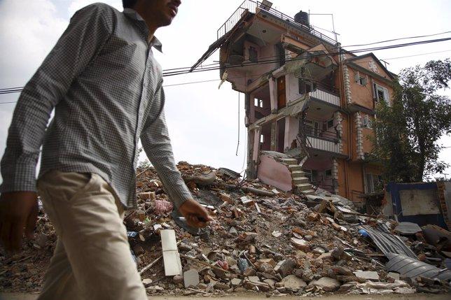 Un hombre delante de un edificio derrumbado por terremoto de Nepal
