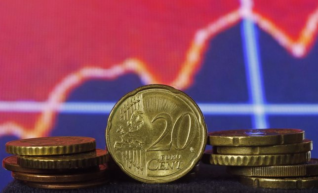 Euro coins are seen in front of displayed stock graph in this picture illustrati