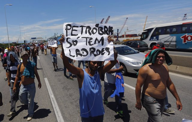 An outsourced worker who was contracted to work for Petrobras holds a placard as