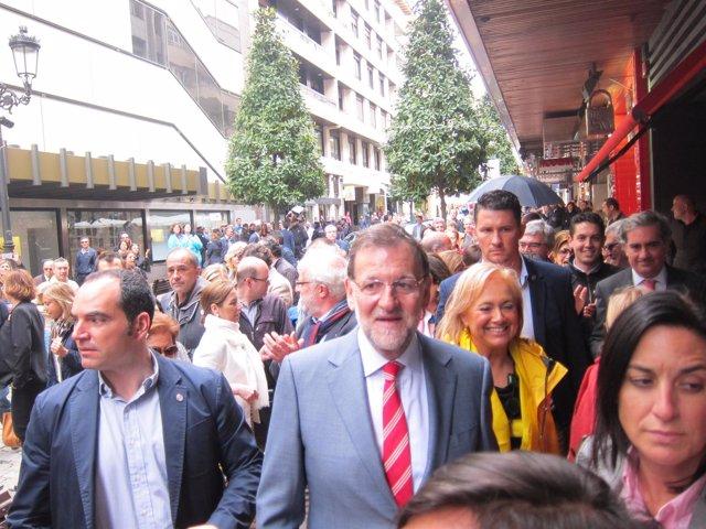 Rajoy, durante su paseo por Oviedo. Al fondo, las protestas.