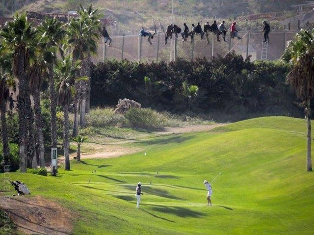 Inmigrantes en la valla de Melilla mientras gente juega al golf