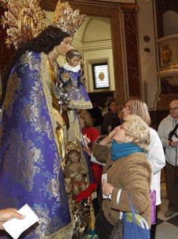 Una mujer del Grao abre el besamanos a la Virgen
