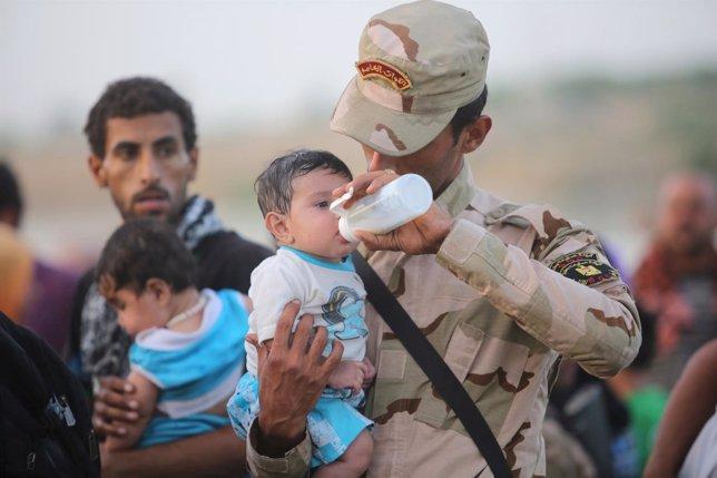 Un soldado iraquí alimenta a un bebé desplazado por el Estado Islámico