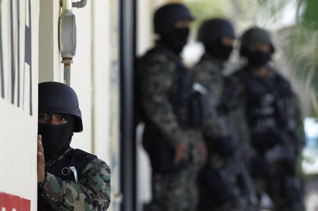 Mexican Marines stand guard at a clinic during an operation in the municipality