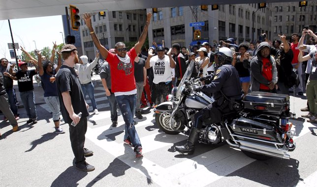 Protestors gather in a downtown intersection as a Cleveland Police officers bloc