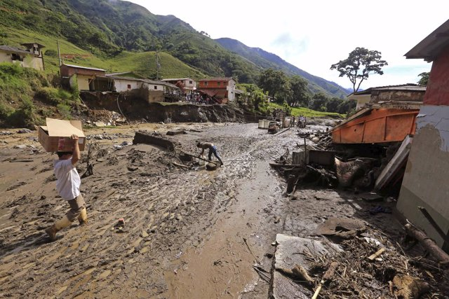 A resident carries supplies at the site where a landslide sent mud and water cra