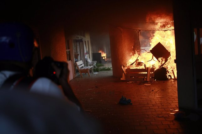A news photographer takes pictures of a fire at the Municipal Palace during a de