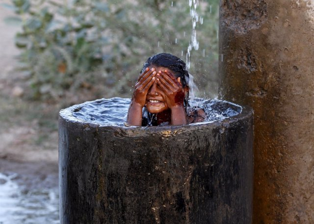 A girl bathes to cool off herself with water that is leaking from a broken pipe