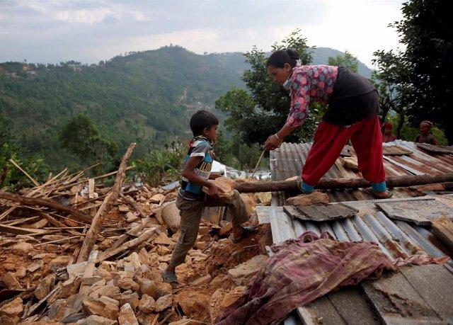 Un niño ayuda a su madre a reconstruir su casa en Sindhupalchowk, Nepal.