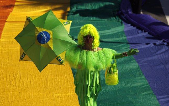 A participant holding an umbrella takes part in a Gay Pride Parade on Copacabana