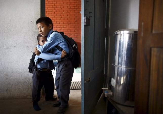 Biyon Karmacharya comforts his brother Saksham from crying as their father leave