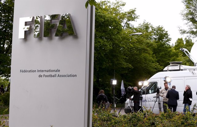 Members of the media stand in front of the entrance of the FIFA headquarters in