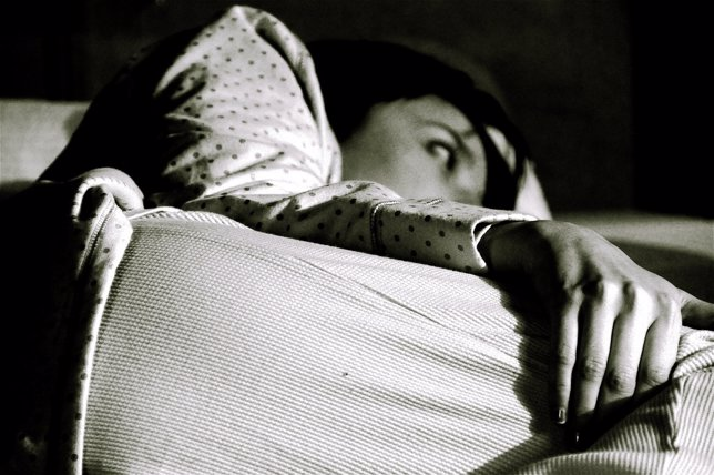 Mujer con insomnio en la cama