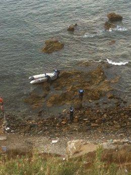 Agentes alrededor de la embarcación en la que han llegado los subsaharianos