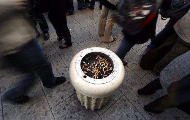 Fumadores frente a un cenicero en la calle