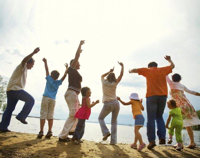 Adultos y niños danzan en la playa. Danza. Baile. Felicidad. Alegría. Gente