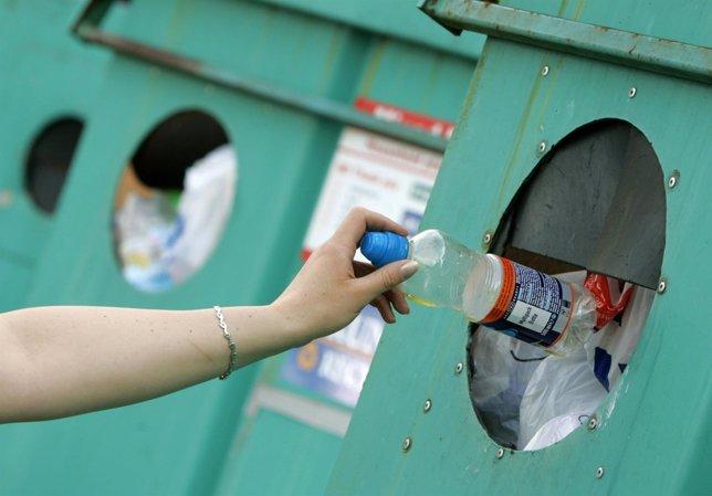 Una mujer tira al contenedor de plático una botella, reciclar, día del planeta