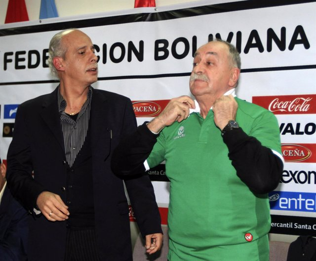 Xavier Azkargorta of Spain adjusts a Bolivia's soccer jersey after being appoint