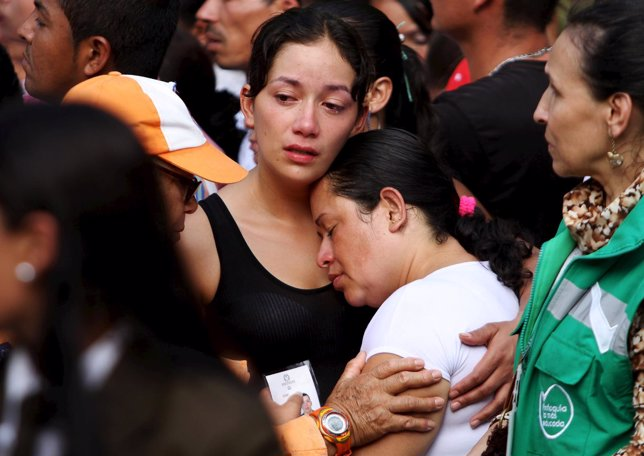 A relative mourns during a mass burial for 33 victims of a recent landslide in S