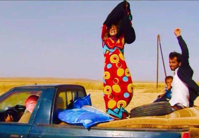 Una mujer se quita los negros ropajes a los que obliga el Estado Islámico