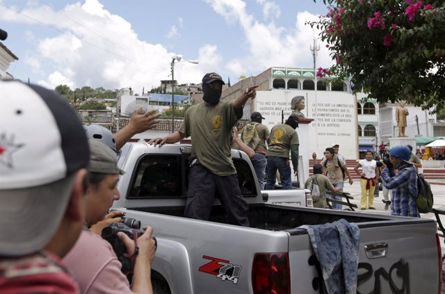 A community policeman on a truck points as he is confronted by Tixtla villagers,