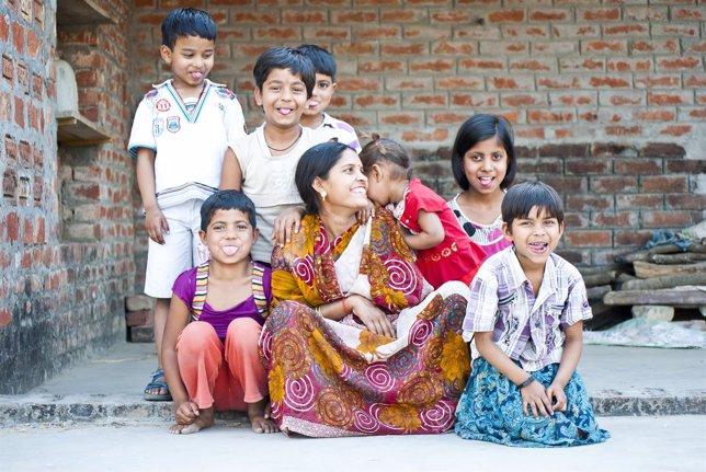 Una mujer con sus dos hijos y niños vecinos en India