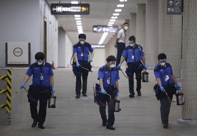 Empleados de servicios de desinfección limpian el suelo del Aeropuerto de Gimpo