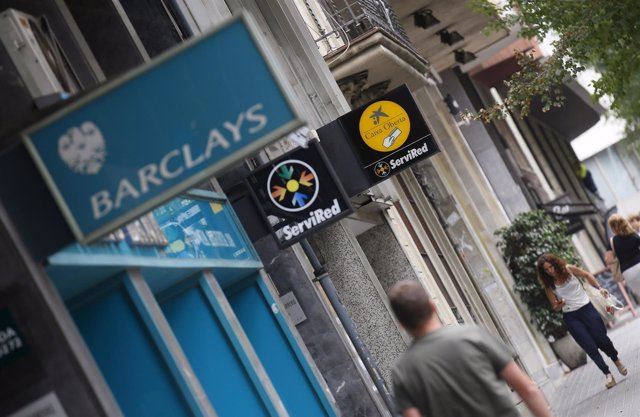 People walk past a LaCaixa and Barclays bank offices in Barcelona