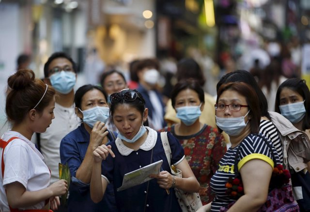 A tourist wearing a mask to prevent contracting MERS asks sales assistant for di