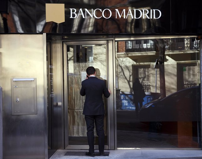 Man enters a Banco Madrid branch with a closed sign on its door in Madrid