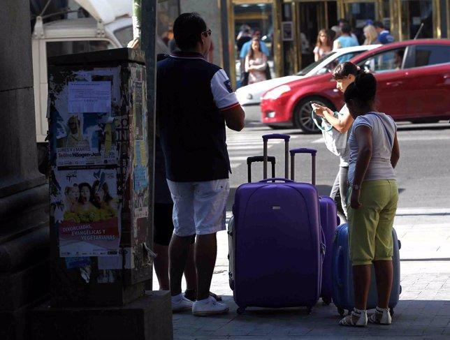 Turismo, turistas, personas en la calle con maletas