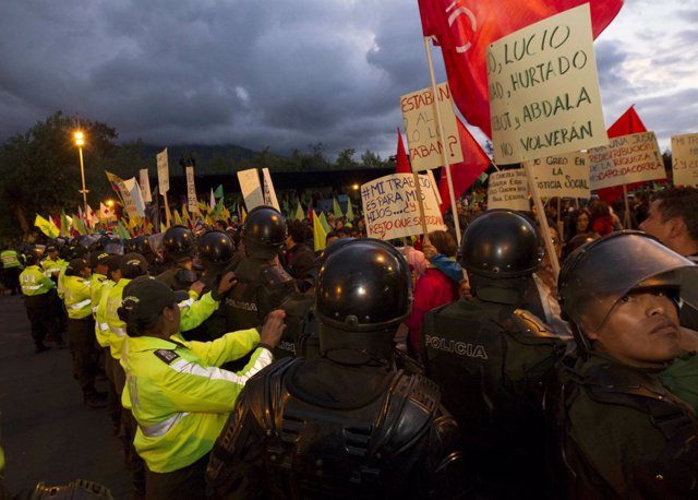 Supporters of Rafael Correa hold placards in Quito