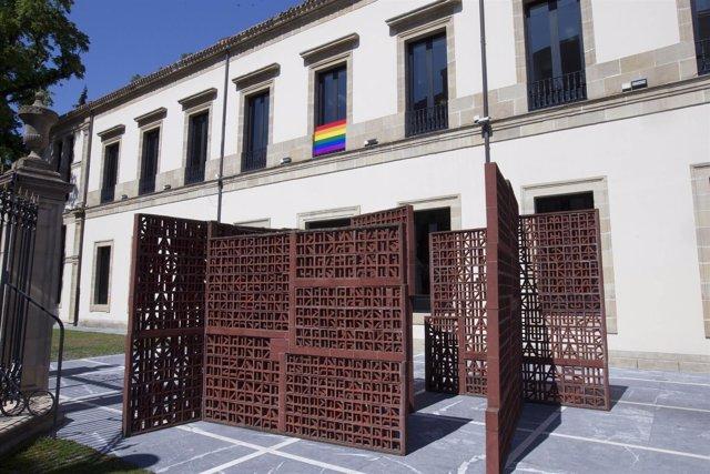 Colocación en fachada del parlamento vasco de la bandera arco iris