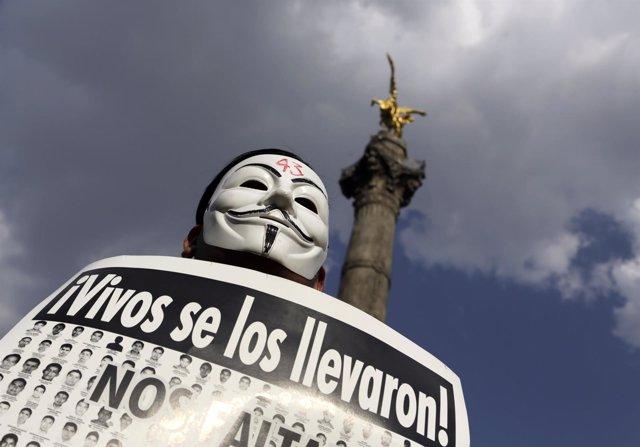 Un manifestante con máscara de Guy Fawkes protesta 42 estudiantes normalistas