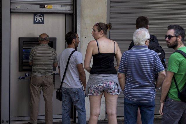 Greigos haciendo cola en un cajero automático de Atenas