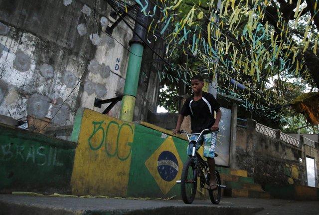 Un niño monta su bicicleta por una calle pintada con la bandera de Brasil