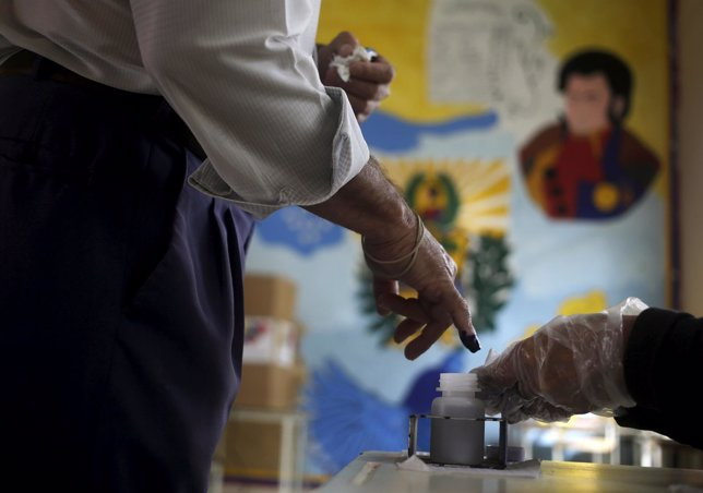 A polling center officer applies ink on a finger of a man after he voted in Cara