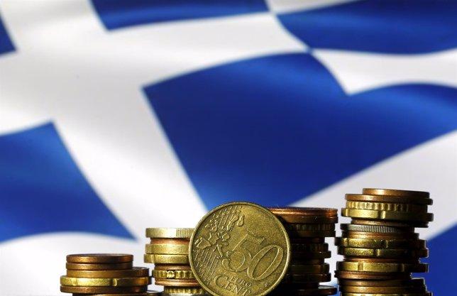 Monedads de euro enfrente de una bandera griega
