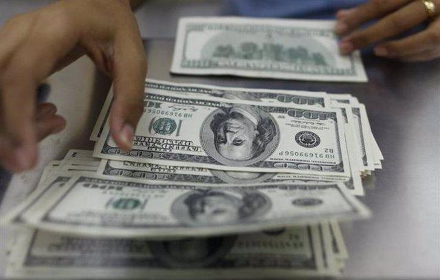 Una mujer cuenta dólares estadounidenses en una casa de cambios en Rangun.