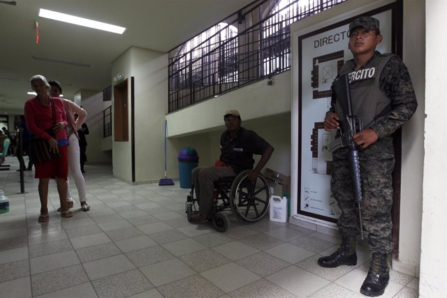 Soldier stands guard as patients are seen at San Felipe hospital in Tegucigalpa