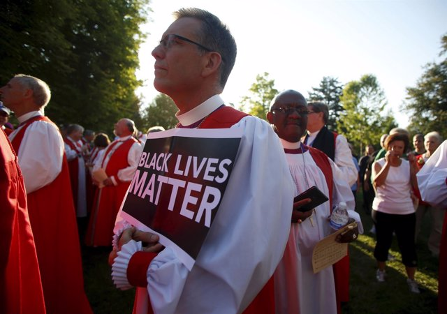 "Bishop Scott Barker holds a ""Black Lives Matter"" sign as he along with approxima"