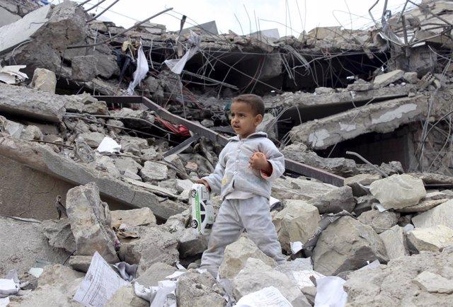 Un niño recoge juguetes entre los escombros de su casa en Yemen