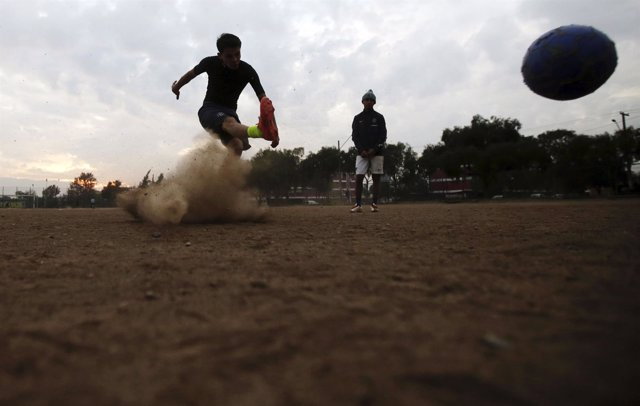 Youths play soccer in Santiago, Chile