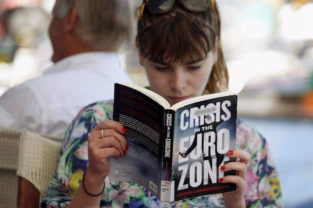 Una mujer lee un libro sobre la crisis griega en Meyisti