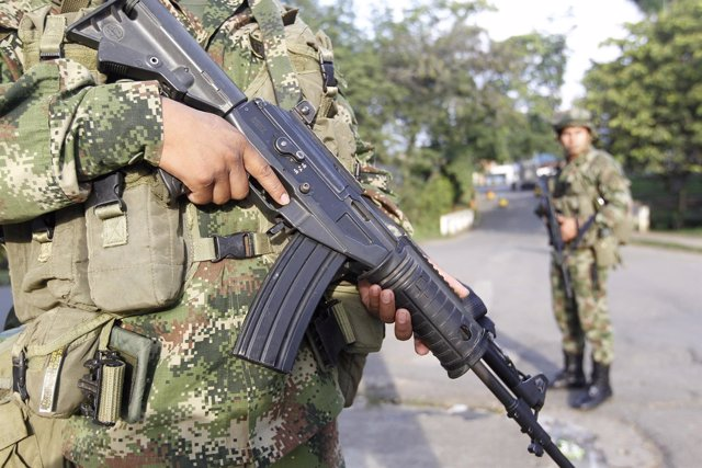 Colombian soldiers stand guard at a street in Caloto