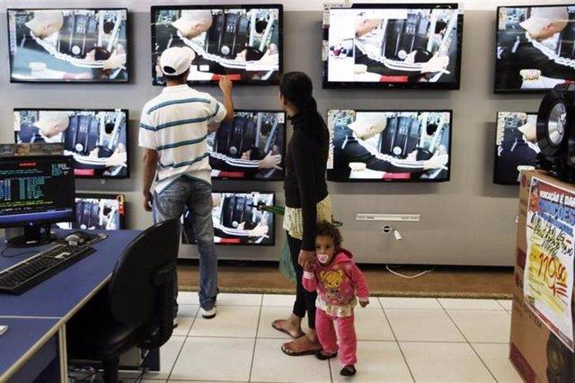 Una pareja junto a su hija miran televisores de pantalla planta en una tienda de