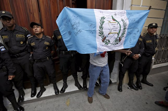 A man holds a Guatemala flag during a demonstration to celebrate the resignatio