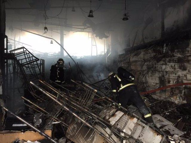 Bomberos extinguen el fuego en el local textil calcinado