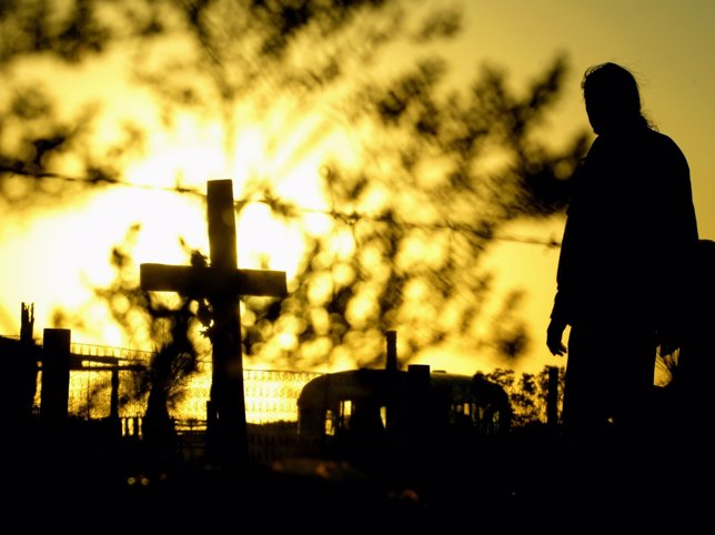 MAN LOOKS AT CROSSES MARKING SPOTS WHERE DEAD WOMEN HAVE BEEN DUMPED IN CIUDAD
