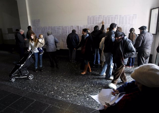 Citizens look for their names before voting in an election for Buenos Aires' Cit